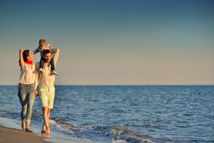 Happy young family have fun on beach run and jump at sunset Stock Image