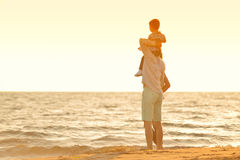 Happy young family have fun on beach run and jump at sunset Royalty Free Stock Photography