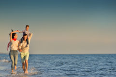 Happy young family have fun on beach run and jump at sunset Royalty Free Stock Photos