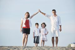 Happy young family have fun on beach at sunset Stock Image