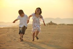 Happy young family have fun on beach at sunset Royalty Free Stock Photos