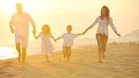 Happy young family have fun on beach at sunset Stock Photography