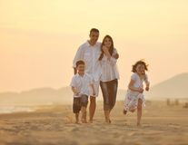 Happy young family have fun on beach at sunset royalty free stock photography