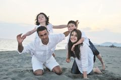 Happy young family have fun on beach at sunset Royalty Free Stock Images