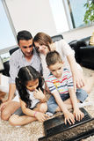 Happy young family have a fun with laptop at home Stock Photo