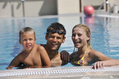 Happy young family have fun on swimming pool. At summer vacation Stock Photos