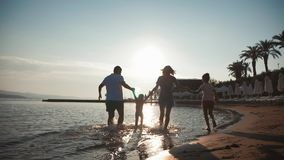 Happy young family have fun walking on beach at sunset. Family silhouette travel holiday.