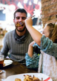 Happy young family having breakfast in the cafe. Royalty Free Stock Photos