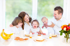 Happy young family having breakfast on Sunday. Happy young family with a teenage boy, cute curly toddler girl and a newborn baby having fun together during an Royalty Free Stock Images