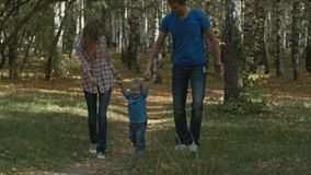 Happy young family is having fun in the autumn park outdoors on a sunny day. Mother, father and their little baby-boy royalty free stock photos