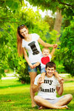 Happy young family is having fun in the green summer park outdoo Stock Image
