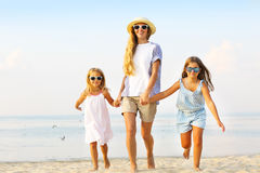 Happy young family having fun running on beach at sunset. Family Royalty Free Stock Images