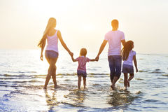 Happy young family having fun running on beach at sunset Royalty Free Stock Photos