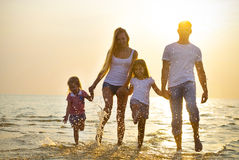 Happy Young Family Having Fun Running On Beach At Sunset. Family Stock Photo