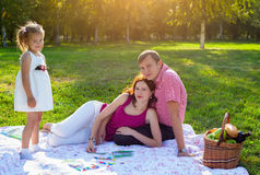 Happy young family having picnic at meadow. At summer day Royalty Free Stock Image