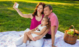Happy young family having picnic at meadow. At summer day. Mother doing selfie with your family Stock Photography