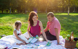 Happy young family having picnic at meadow. At summer day. mother playing with her daughter Royalty Free Stock Image