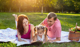 Happy young family having picnic at meadow. At summer day. Mother reading a book with her little daughter Stock Images