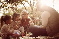 Happy family having picnic together in park. Happy young family having picnic together in park stock photography