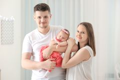 Happy young family holding cute sleeping newborn baby at hom royalty free stock photo