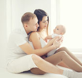Happy young family at home in white room near window, parents Royalty Free Stock Image