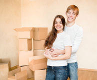 Happy young family hugging on a background of cardboard boxes Royalty Free Stock Photos