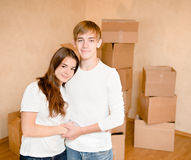Happy young family hugging on a background of cardboard boxes Stock Photography