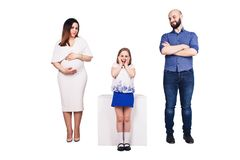Happy young family isolated over white background. Bearded father, pregnant mother and happy daughter. stock images
