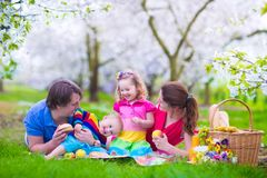 Happy young family with kids having picnic outdoors. Young family with kids having picnic outdoors. Parents with two children relax in a blooming summer garden Stock Image