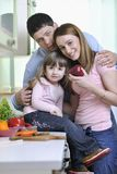 Happy young family in kitchen Stock Photos