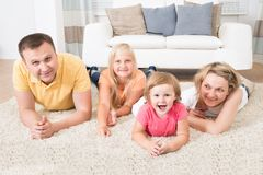 Happy young family laying on carpet Royalty Free Stock Images