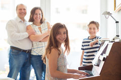 Happy young family listening how cildren plays piano music. At home royalty free stock photo