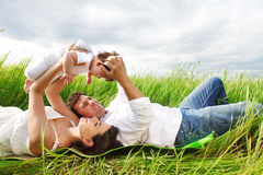 Happy young family with little baby girl Stock Photos