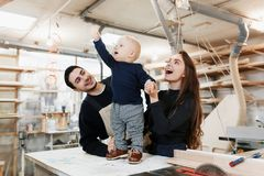 Happy young family with the little son in the carpenter workshop royalty free stock photography