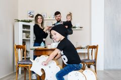 Happy young family and little son poses on rocking horse at home. Horizontal portrait royalty free stock image