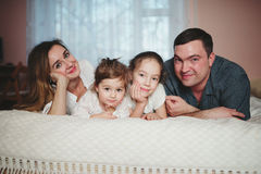 Happy young family lying in bed Stock Photography