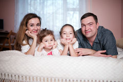 Happy young family lying in bed Royalty Free Stock Photography
