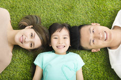 Happy  Young  Family lying on the grass Stock Photo