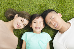 Happy Young Family lying on the grass royalty free stock image