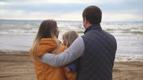 Happy young family. Man with woman and little girl standing on the ocean shore stock video footage