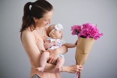 Happy young family. Mom and baby playing with flowers Stock Images