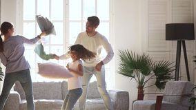 Happy mom dad and little kid daughter having pillow fight. Happy young family mom dad and little kid daughter having fun pillow fight in living room, cheerful stock video