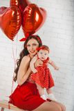 Happy young family mother and daughter posing in studio. royalty free stock photo