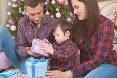 Happy young family mother father and child with christmas gift b royalty free stock images