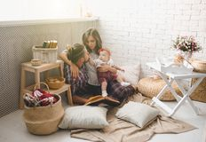 Happy young family mother, father and daughter playing on carpet at home. stock photo