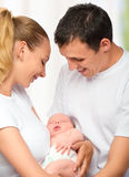 Happy young family of mother, father and newborn baby in their a Royalty Free Stock Photos