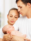 Happy young family of mother, father and newborn baby in their a Royalty Free Stock Photography