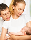 Happy young family of mother, father and newborn baby in their a Stock Photos