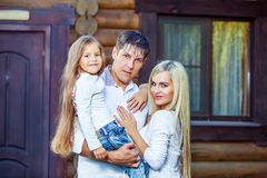 Happy young family near the wooden house Royalty Free Stock Images
