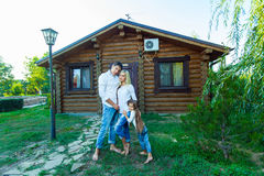 Happy young family near the wooden house Stock Photography